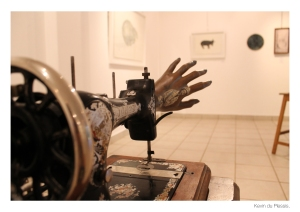 """The turn of instrumental reason (2014) series of altered sewing machines relates thematically to The Bleek house focus on the animalisation of difference. Similar to The Bleek house works these mechanical assemblages feature paintings on the palms of the mannequin hands of animal and therianthropic forms drawn from San rock paintings; coupled with images of individuals from the colonial African stage. Further to this narrative element the grafted together 'machine arm' and artificial hand evokes: the violent stitch of the sewing machine (with monstrous surgical inference); industrialisation (the product of enlightenment thinking); histories of western dominance and exploitation; the punitive violence perpetrated against Africans in the name of industry during colonial times. Also significant is the coupling of the feminine hands with the feminine ergonomics of the sewing machines. This is suggestive of the female hands that these well worn objects (haunted by the marks of past users) were designed to respond to and enspan. The presence of animal forms on the palms of the hands alludes to the rationalised binary opposition of nature and culture/industry; and the predjudical association of women with the 'lesser'form of nature. The animal forms on the part of these mechanically driven hands that would be used to crush something alludes to the destruction and brutal exploitation of nature by the 'wheels of industry'."" -from the catalogue Wolf in Sheep's Clothing."